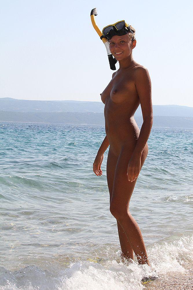 Голые нудисты прекрасно проводят время на пляже
