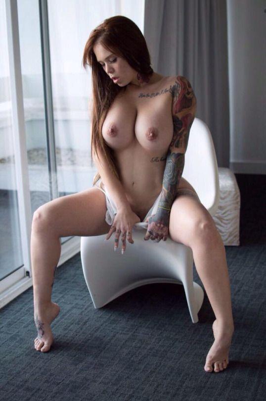 Рыжая с татуировками девушка позирует голышом