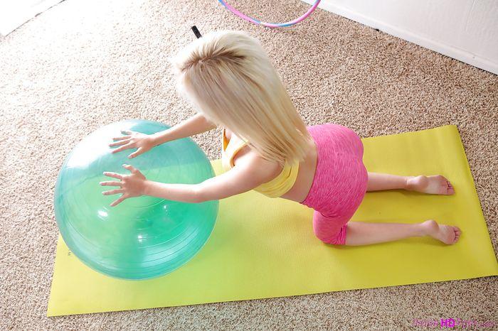 Голая гимнастка разминается на коврике